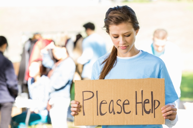 Teen volunteer holding PLEASE HELP sign at outdoor donation drive